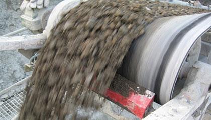 Basaltsteine und Diabas läuft über ein Förderband mit Abstreifkante